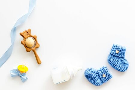 Blue knitted footwear for kids, dummy, rattle and bottle on white background top view space for text Stockfoto