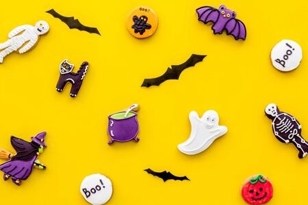 Creepy cookies for halloween treat pattern on yellow background top view
