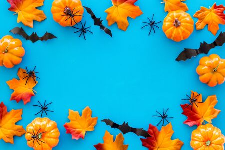 Halloween frame with pumpkins, spiders and bats on blue background top view copy space