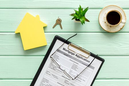 House mortgage with application, glasses, coffee, house toy, keys on mint green wooden banker desk background top view Stok Fotoğraf - 129786987