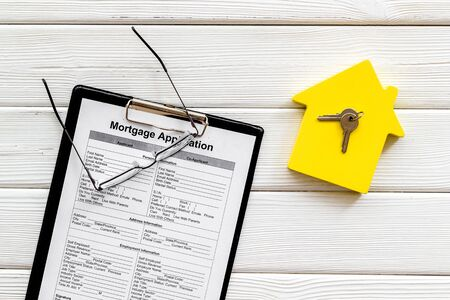House mortgage with application, glasses, house toy, keys on white wooden banker desk background top view Stok Fotoğraf