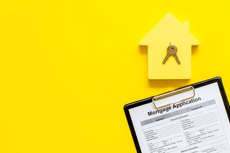 House mortgage with application, house toy, keys on yellow banker desk background top view mock up Stok Fotoğraf - 129786990