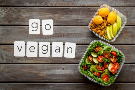Lunch box with salad and go vegan text on wooden background top view