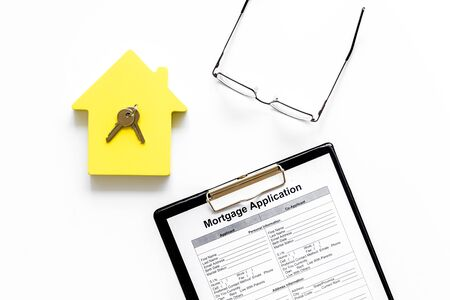 Mortgage application with glasses, house figure and keys on white background top view