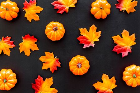Autumn composition. Pattern with red and orange leaves and pumpkins on black background top view Stok Fotoğraf