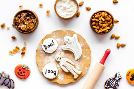 spooky halloween figures with rolling pin, flour, sugar, almond for cooking treat on white background top view
