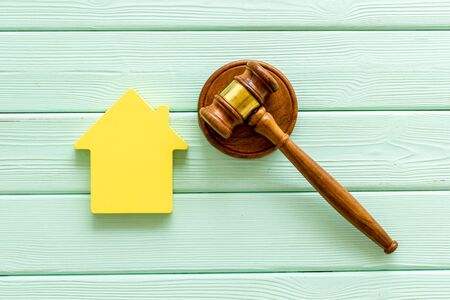Inscribed gavel, house figure for inheritance concept on mint green wooden background top view Stok Fotoğraf - 129787250