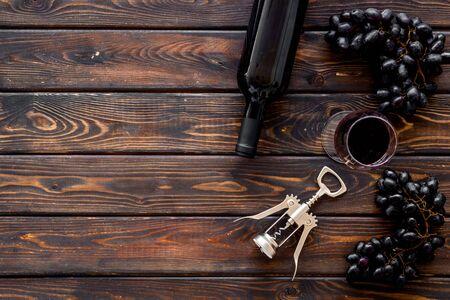 Red wine bottle near wineglass on dark wooden background top view copy space Фото со стока - 129787263