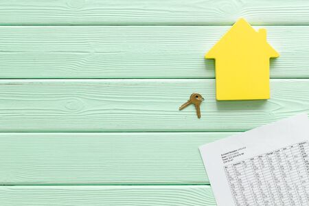 Tax for property accounting with house figure, keys and table on mint green wooden background top view copyspace
