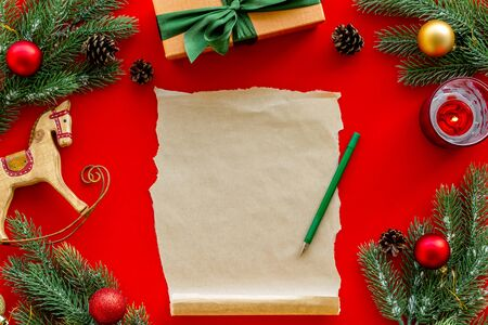 Letter to Santa Claus concept. Paper on red background with New Year decoration top view mockup space for text 写真素材