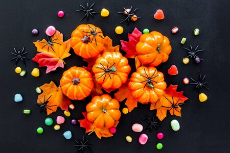 Bright Halloween composition with sweets and pumpkins on black background top view Stok Fotoğraf