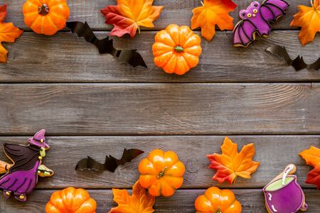 Bright Halloween composition with sweets and pumpkins on dark wooden background top view frame copy space Imagens