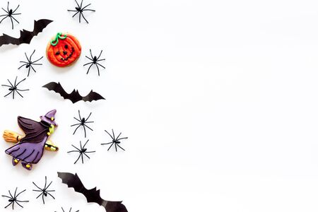 Cute Halloween decoration. Bats, spiders and special cookies on white background top view copy space Stock Photo