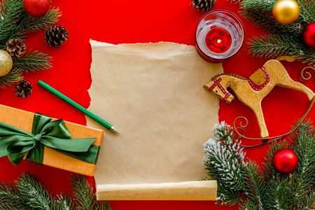 Letter to Santa Claus concept. Paper on red background with New Year decoration top view mockup space for text Фото со стока