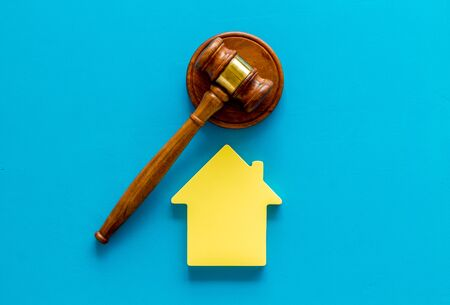 Inheritance of the house concept with figure and gavel on blue background top view Banco de Imagens