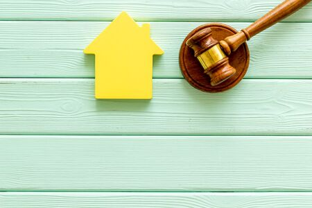 Inheritance of the house concept with figure and gavel on mint green wooden background top view space for text