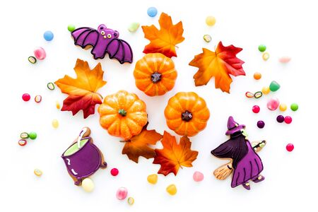 Nice halloween background with sweets. Cookies and pumpkins on white top view