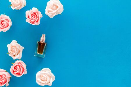 Perfume and flowers composition on blue background top view pattern frame space for text