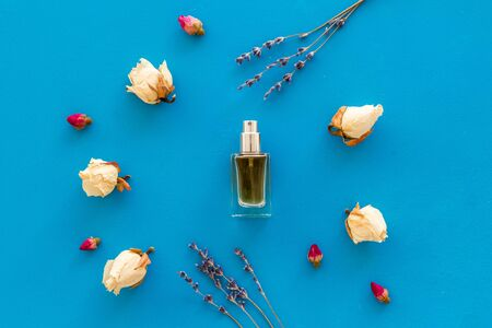 Perfume and flowers composition on blue background top view pattern frame Stock fotó