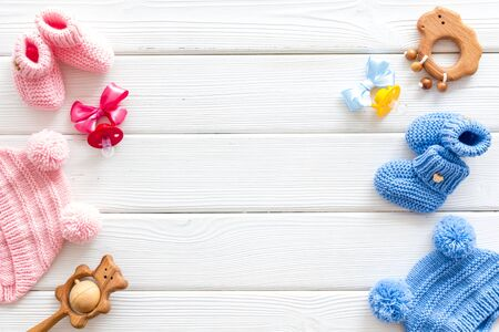 Blue and pink knitted footwear, hat, dummy, rattle frame for baby on white wooden background top view mock up Stock Photo