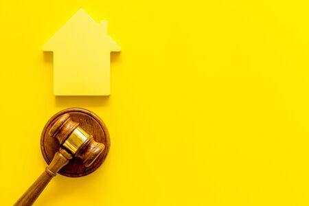 Inscribed gavel, house figure for inheritance concept on yellow background top view copyspace Stock Photo