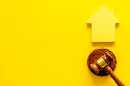 Inheritance of the house concept with figure and gavel on yellow background top view space for text 스톡 콘텐츠
