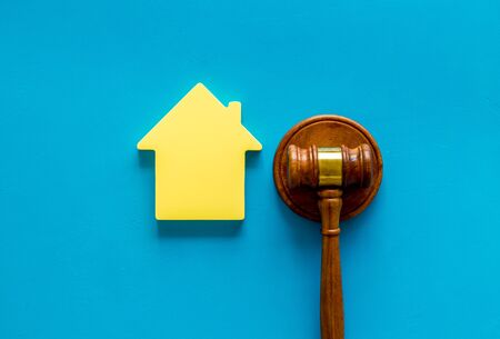 Inscribed gavel, house figure for inheritance concept on blue background top view 스톡 콘텐츠