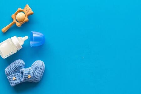 Blue knitted footwear and rattle, bottle for baby on blue background top view mock up Stock Photo