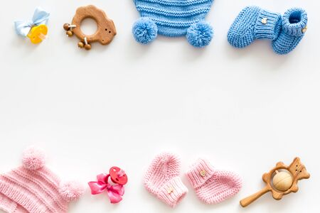 Blue and pink knitted footwear, hat, dummy, rattle frame for baby on white background top view mock up