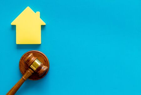 Inheritance of the house concept with house figure and inscribed gavel on blue background top view space for text