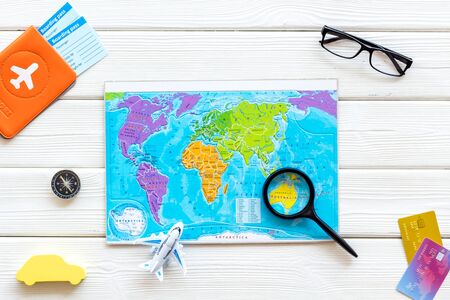 Planning a travel concept. Map of the world and tourist accessories on white wooden background top view