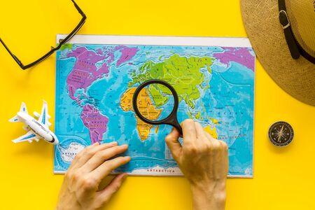 Planning a travel concept. Map of the world and tourist accessories on yellow background top view 版權商用圖片