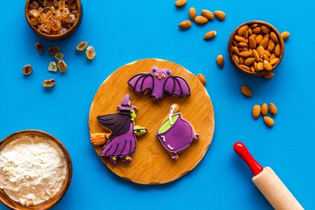spooky halloween figures with rolling pin, flour, sugar, almond for cooking treat on blue background top view