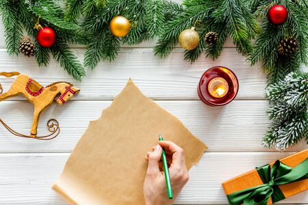 Letter to Santa Claus concept. Paper on white wooden background with New Year decoration top view mockup copy space