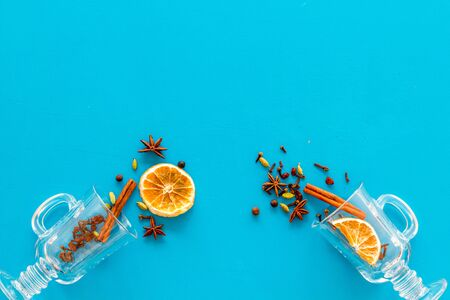Mulled wine concept. Spices and dried orange in glasses on blue background top view space for text