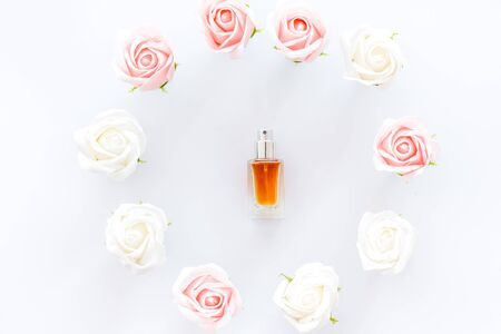Perfume and flowers composition on white background top view pattern frame