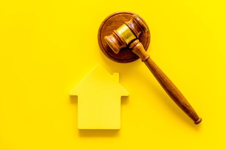 Inscribed gavel, house figure for inheritance concept on yellow background top view