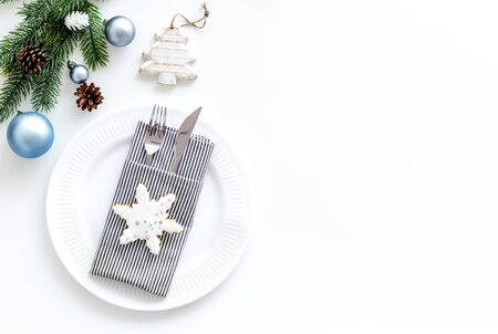 Table setting for new year with pine branch, decorations, plate and tableware white background top view copyspace