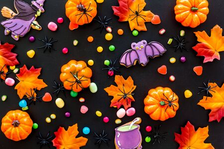 Nice halloween background with sweets. Cookies and pumpkins on black top view pattern