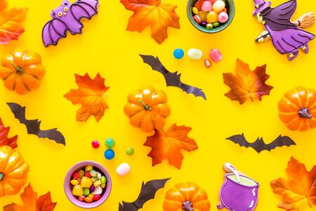 Nice halloween background with sweets. Cookies and pumpkins on yellow top view