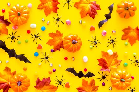 Bright Halloween composition with sweets, bats and pumpkins on yellow background top view pattern