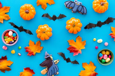 Nice halloween background with sweets. Cookies and pumpkins on blue top view pattern