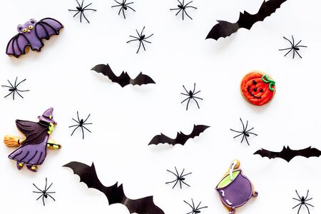 Cute Halloween decoration. Bats, spiders and special cookies on white background top view pattern Stock Photo