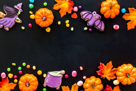 Bright Halloween composition with sweets and pumpkins on black background top view frame
