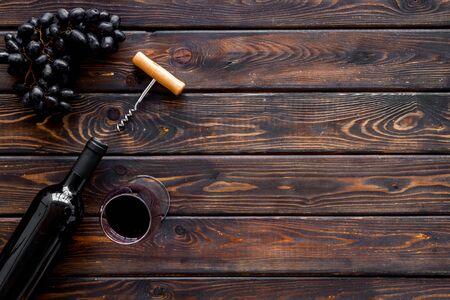 Testing wine concept. Wine bottle near black grape, wineglass and corkscrew Фото со стока - 129972812