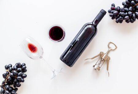 Testing wine concept. Wine bottle near black grape, wineglass and corkscrew