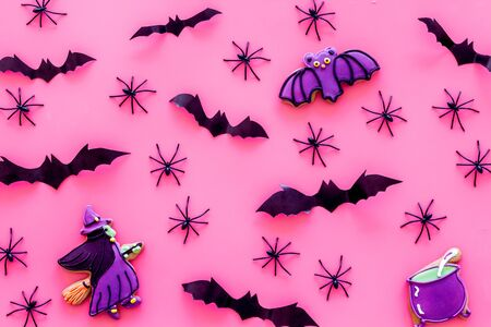 Cute Halloween decoration. Bats, spiders and special cookies on pink background top view. Stock Photo