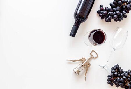 Red wine bottle near grape, wineglass and corkscrew Фото со стока - 129972905