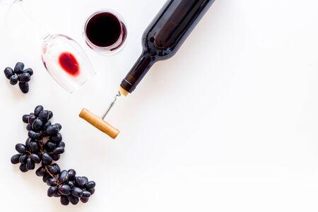 Red wine bottle near grape, wineglass and corkscrew Фото со стока - 129972907
