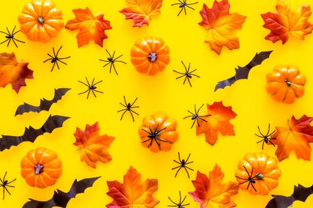 Halloween pattern with pumpkins, spiders and bats on yellow background top view.